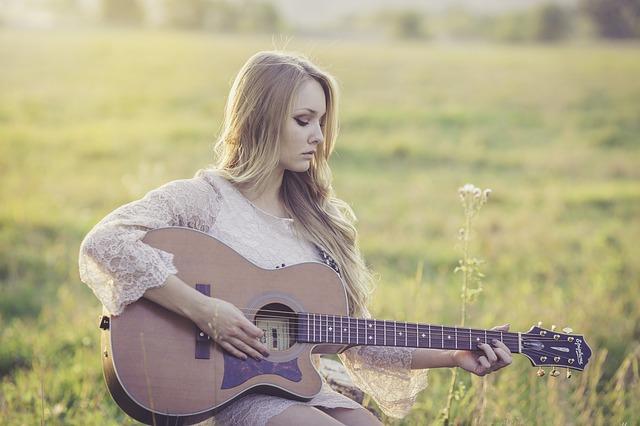 dívka s kytarou na louce