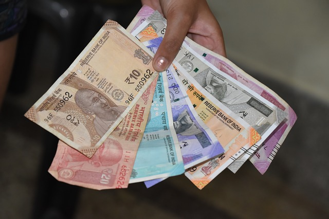 ruka plná indických bankovek